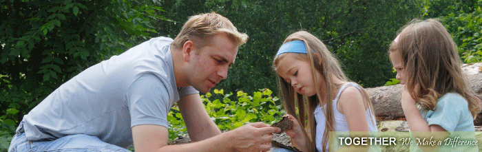 A father showing his daughters a leaf